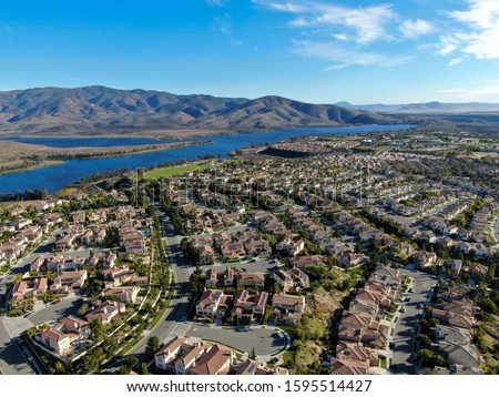 Aerial view of identical residential subdivision house with big lake and mountain on the background during sunny day in Chula Vista, California, USA. Royalty-Free Stock Photo #1595514427