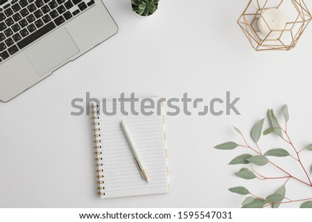Notebook with pen, candle, small domestic plant, branch with green leaves and laptop keypad on white desk #1595547031