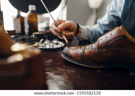Bootmaker with brush tints shoes, footwear repair Royalty-Free Stock Photo #1595582128