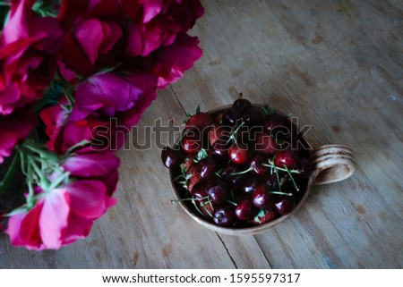 Ripe cherries or cherries in a cup on a wooden table with a bouquet of red flowers in a vase. Top view. The mood and females of a warm summer with a rich harvest. #1595597317