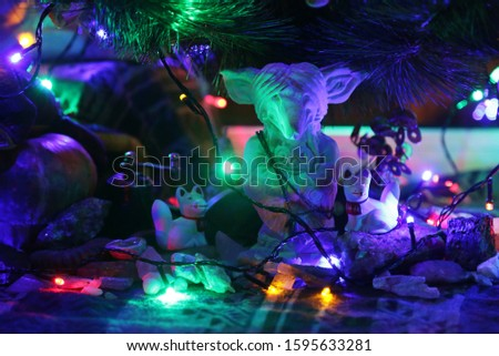 Close-up view of  handmade statuette of stylized fox as a christmas decoration under Christmas tree. This fox is ''soul guide '' in magic world. All objects are illuminated by electric garland.