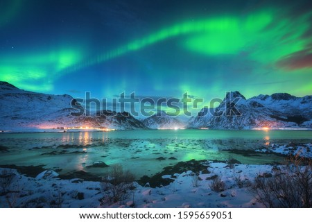 Aurora borealis over the sea coast, snowy mountains and city lights at night. Northern lights in Lofoten islands, Norway. Starry sky with polar lights. Winter landscape with aurora reflected in water #1595659051