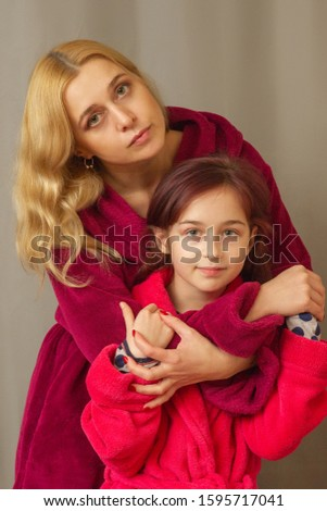 Mom and daughter in warm bathrobes. warm relations between mother and daughter. spend time together. body care . are pointed at the camera. picture for memory. Elegant mothe with little daughter.