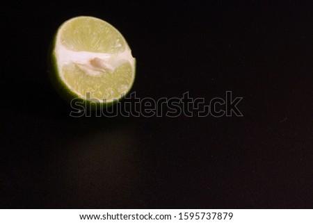 Half Green Lemon. Half of a lemon. Half of lemon isolated on black a ฺbackground #1595737879