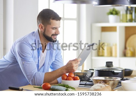 Man following recipe on digital tablet and cooking tasty and healthy food in kitchen at home #1595738236