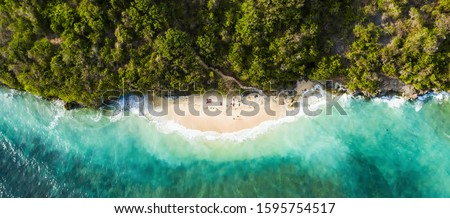 View from above, stunning aerial view of some tourists sunbathing on a beautiful beach bathed by a turquoise rough sea during sunset, Green Bowl Beach, South Bali, Indonesia. #1595754517