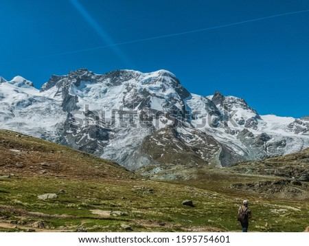 The beautiful view of the iceberg with a clear sky. Blue sky and clear air. The green meadow of winter. There are many rocks along the mountains and meadows. Suitable for people who like to walk. #1595754601