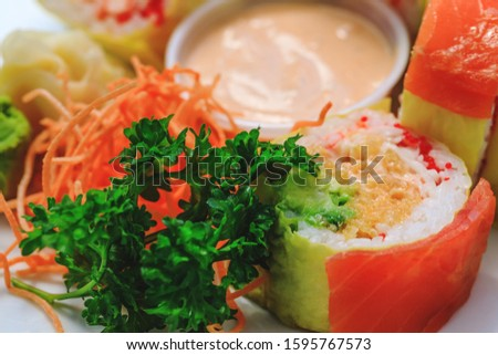 Shrimps with rice and parsley in close-up image. Sashimi sushi in close up picture. Plate of seafood. Fresh and delicious maki, nigiri sushi and sake glass.