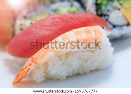 Shrimp with rice in close-up image. Sashimi sushi in close up picture. Plate of shrimps. Fresh and delicious maki and nigiri sushi and sake glass.
