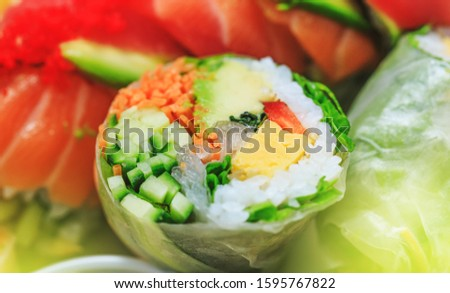 Fresh sushi with cucumber maki, carrot, sea cabbage and salmon maki. Japanese sashimi sushi rolls with salmon roe in close up picture. Donburi in asian style food. Shrimp with rice in close-up image.