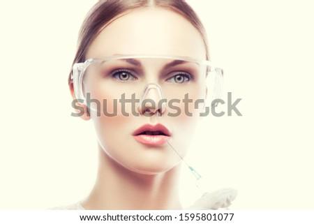 Beautician plastic surgeon show to patient lip injection. Copy space #1595801077