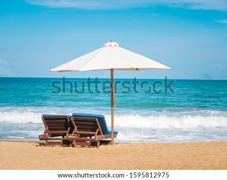 Chairs and umbrella on the beach near ocean. Winter vacation in hot places. Sunshine and moody sky #1595812975