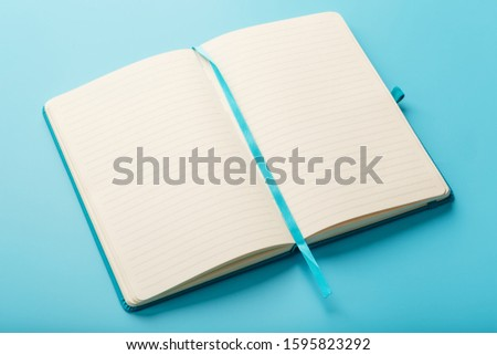 Open notebook, diary with blank and blank pages on a blue background, top view. Layout for design, free space #1595823292
