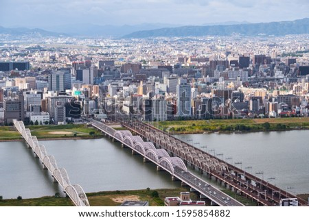 OSAKA, JAPAN - OCTOBER 15, 2019: The view of megapolis and Yodo River  with the Yodo Bridge, Juso-o bridge and subway bridges from the Umeda Sky Building Observatory. Osaka. Japan #1595854882