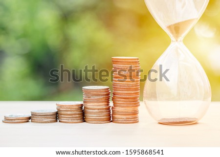 money times memory concept, coins stack with sand hourglass #1595868541