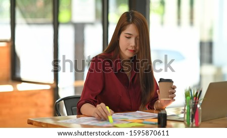 Young creative woman selected colour guide with holding coffee cup. #1595870611