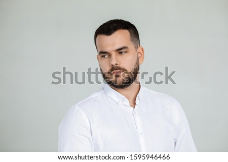 portrait of sad bearded man in white shirt on gray background #1595946466