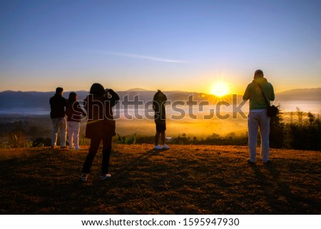 Mae Hong Son, Thailand ; December 18, 2019: Silhouette of group tourist take photo on a hill , sunrise with mountain and fog  at viewpoint, Mae Hong Son ,Thailand #1595947930