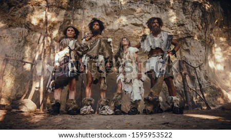 Tribe of Four Hunter-Gatherers Wearing Animal Skin Holding Stone Tipped Tools, Pose at the Entrance of their Cave. Portrait of Two Grown Male and Two Female Neanderthals and their Way of Living #1595953522