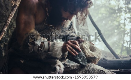 Primeval Caveman Wearing Animal Skin Hits Rock with Sharp Stone and Makes Primitive Tool for Hunting Animal Prey. Neanderthal Using Hand axe to Create first Wheel. #1595953579