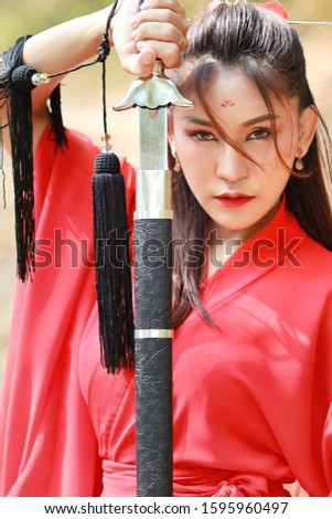 Young beautiful asian woman dressing in traditional Chinese old fashion warrior style with ancient word. Full length cute girl in red dress looking at camera in nature outdoor. Travel in Asia concept #1595960497