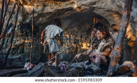 Tribe of Hunter-Gatherers Wearing Animal Skin Live in a Cave. Leader Brings Animal Prey from Hunting, Female Cooks Food on Bonfire, Girl Drawing on Wals Creating Art. Neanderthal Homo Sapiens Family #1595983309