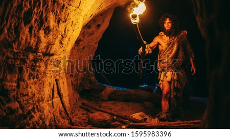 Primeval Caveman Wearing Animal Skin Exploring Cave At Night, Holding Torch with Fire Looking at Drawings on the Walls at Night. Neanderthal Searching Safe Place to Spend the Night #1595983396