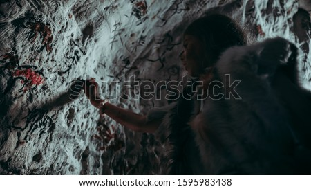 Primitive Prehistoric Neanderthal Child in Animal Skin Draws Animals and Abstracts on Walls at Night. Creating Cave Art with Petroglyphs, Rock Paintings Illuminated by Fire. Low Angle with Cold Light