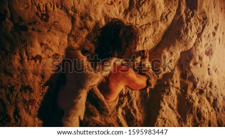 Primitive Prehistoric Neanderthal Wearing Animal Skin Draws Animals and Abstracts on the Walls at Night. Creating First Cave Art with Petroglyphs Rock Paintings Illuminated by Fire. Back View