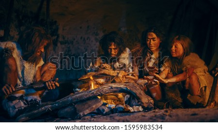 Neanderthal or Homo Sapiens Family Cooking Animal Meat over Bonfire and then Eating it. Tribe of Prehistoric Hunter-Gatherers Wearing Animal Skins Grilling and Eating Meat in Cave at Night #1595983534