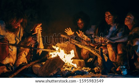 Neanderthal or Homo Sapiens Family Cooking Animal Meat over Bonfire and then Eating it. Tribe of Prehistoric Hunter-Gatherers Wearing Animal Skins Eating in a Dark Scary Cave at Night #1595983549