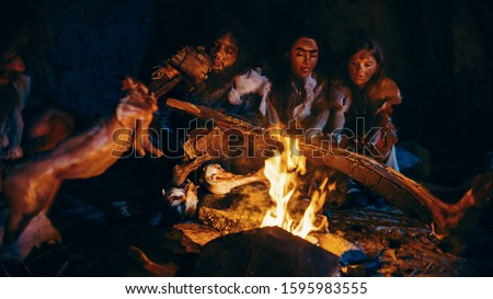 Neanderthal or Homo Sapiens Family Cooking Animal Meat over Bonfire and then Eating it. Tribe of Prehistoric Hunter-Gatherers Wearing Animal Skins Eating in a Dark Scary Cave at Night #1595983555