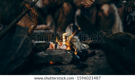 Close-up of Tribe Prehistoric Hunter-Gatherers Trying to Get Warm at the Bonfire, Holding Hands over Fire, Cooking Food. Neanderthal or Homo Sapiens Family Live in Cave at Night. Royalty-Free Stock Photo #1596021487