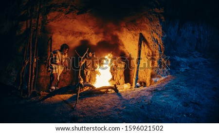 Tribe of Prehistoric Hunter-Gatherers Wearing Animal Skins Stand Around Bonfire Outside of Cave at Night. Portrait of Neanderthal / Homo Sapiens Family Doing Pagan Religion Ritual Near Fire #1596021502
