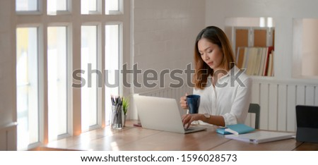 Portrait of young beautiful asian businesswoman working on her project and drinking a coffee  #1596028573