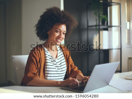 Young female entrepreneur browsing on laptop in the office.