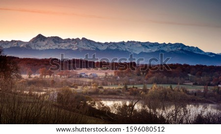 typical French village in the Béarn region with the snow Pyrenees mountains and the Pic du Midi of Bigorre in background