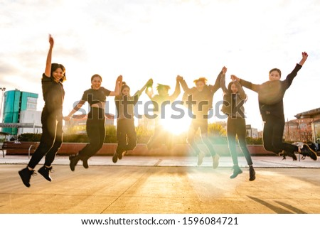 Young Asian friends jumping at sunset. Chinese team winning