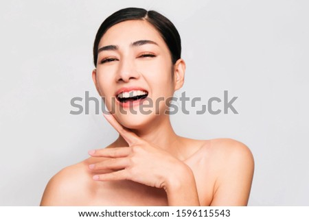 Young beautiful asian woman with clean and bright skin, Cosmetic Beauty Concept,hands touch on the cheek, smiling and friendly face isolated on grey background #1596115543