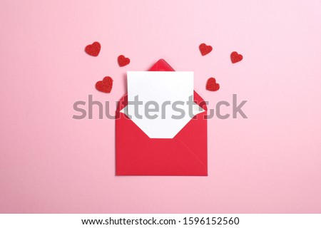Red paper envelope with blank white note mockup inside and Valentines hearts on pink background. Flat lay, top view. Romantic love letter for Valentine's day concept. Royalty-Free Stock Photo #1596152560