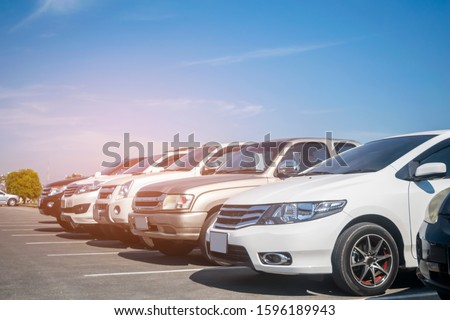 Cars parking in asphalt parking lot in a row with blue sky background. Outdoor parking lot with fresh ozone, green nature environment of transportation and technology concept #1596189943