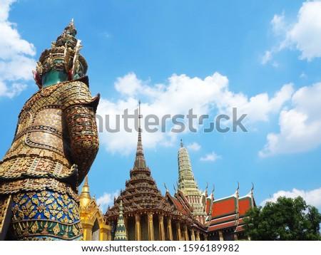 Beautiful pagoda and Thai giant guardian with beautiful blue sky. #1596189982