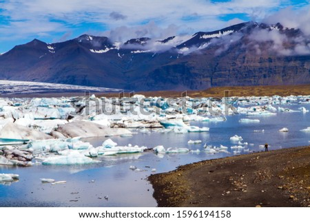Iceland. Skaftafell Park. The lagoon Jokulsaurloun. The lagoon is surrounded by mountains. White and blue icebergs and ice floes reflected in the water. The concept of northern and photo touris #1596194158