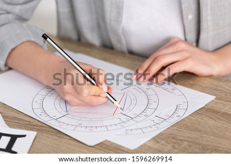 Cropped view of astrologer drawing natal chart on wooden table Royalty-Free Stock Photo #1596269914