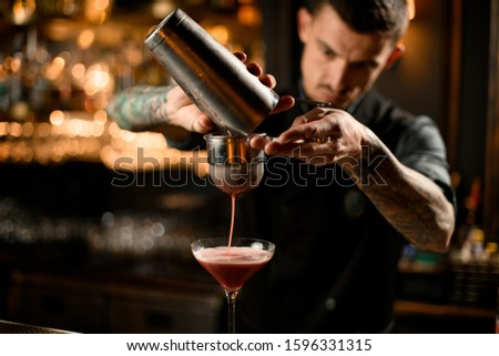 Bartender with goatee pouring tasteful cocktail from shaker through sieve #1596331315