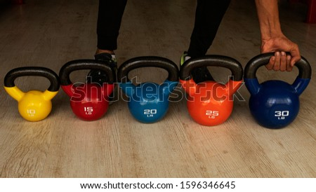 A person trying out a 30 lb kettle bell for workout. This image is best suited to show progression in workouts using different weights. #1596346645