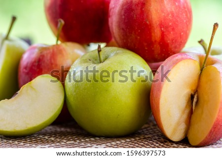 Green apples and red apples placed on the table #1596397573