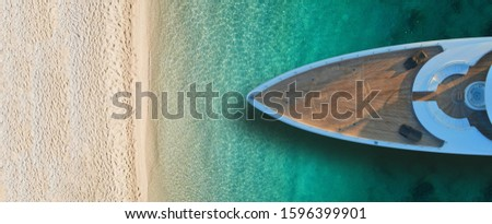 Aerial drone top view ultra wide photo of luxury yacht docked near exotic sandy turquoise beach Royalty-Free Stock Photo #1596399901
