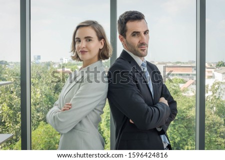 Men and women in the airs, business people standing, arms crossed, looking back and looking at the camera. The dress looks good and is reliable. With a transparent glass backdrop Can see the scenery #1596424816