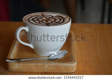 Hot latte coffee in white cup and clean wooden plate. #1596443317